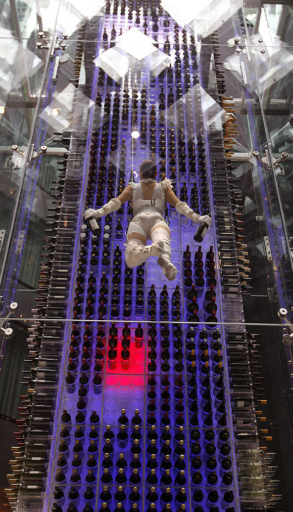 A so-called 'wine angel' carries two bottles of wine as she is suspended by steel ropes and lifted up by a motorised winch in front of a wine storage tower in the lobby of the Radisson Blu Hotel at Zurich airport.