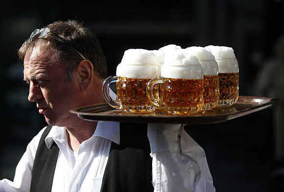 A waiter serves beer in a garden restaurant in Vienna.