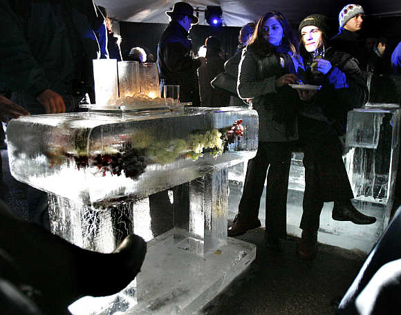 Wine enthusiasts sit on ice furniture in the tasting tent at the outdoor tasting session of the Niagara Grape and Wine Festival in Niagara-on-the-Lake, Canada.