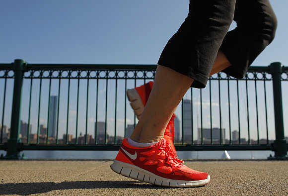 A jogger wearing Nike shoes runs along the Charles River in Cambridge, Massachusetts.