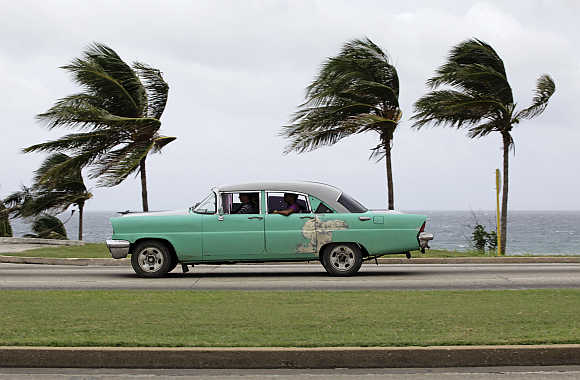 People ride a taxi as strong winds blow palm trees in Havana.