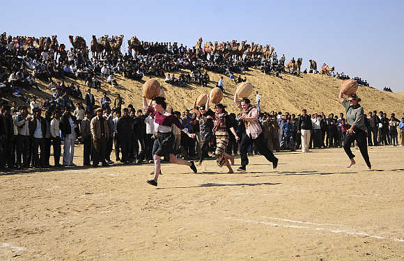 Tourists carry earthen pitchers on their heads as they participate in the 'Matka Race' at Ladera village near Bikaner in Rajasthan.