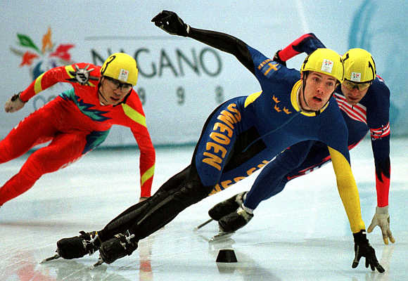 Sweden's Martin Johansson, centre, leads Andrew Gabel of the US, right, and Feng Kai of China, left. during the Olympic men's 1000 metre short track speed skating race in Nagano, China.