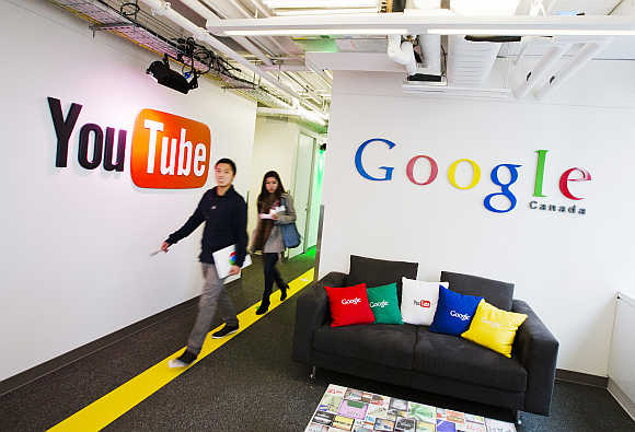 People walk by a YouTube sign at the Google office in Toronto, Canada.