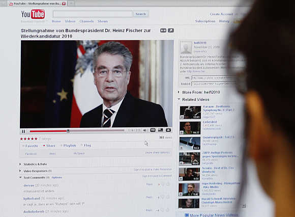 A journalist watches a video of Austrian President Fischer's announcement to run for President on YouTube in Vienna.