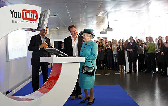 Britain's Queen Elizabeth uses a computer to upload a video to the Royal Channel on YouTube in London.