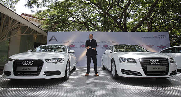 Michael Perschke, head of Audi India, poses between an Audi A6 and an Audi A8L in Mumbai.