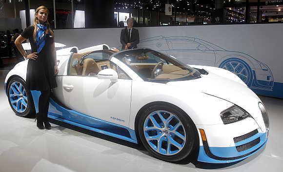 A model stands next to the Bugatti Veyron Grand Sport Vitesse in Doha, Qatar.