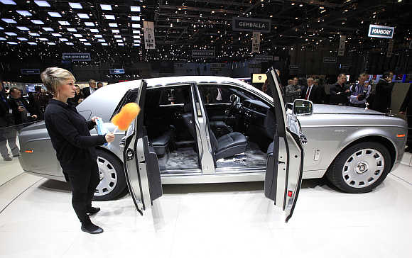 A worker cleans the Rolls Royce Phantom Series II in Geneva, Switzerland.