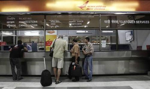 Passengers stand outside the Air India counter at the domestic airport in New Delhi.