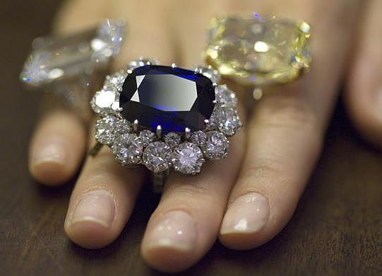 A Christie's employee wears a sapphire (33.23 carats) and diamond ring by Repossi (centre).