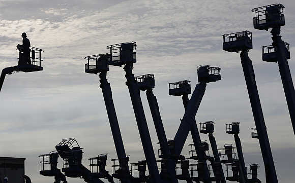 A worker stands on a crane at a construction site at Keihin industrial zone in Kawasaki, south of Tokyo.