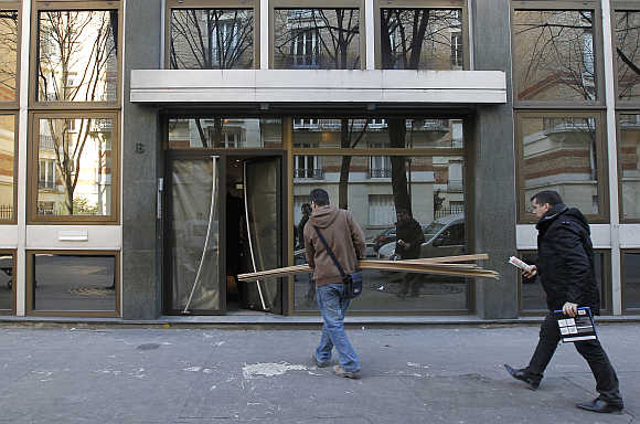 Construction workers enter a building in Paris.