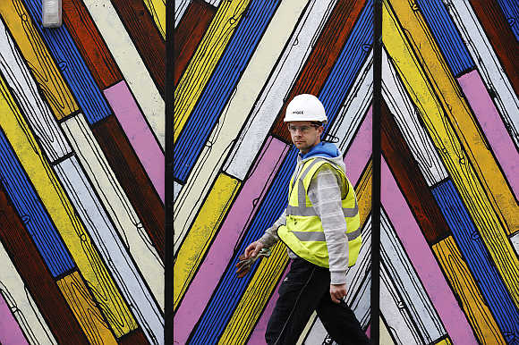 A construction worker walks past a colourful hoarding in the city of London.