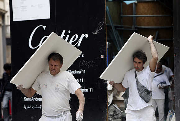 Workers carry materials outside a construction site in downtown Milan.