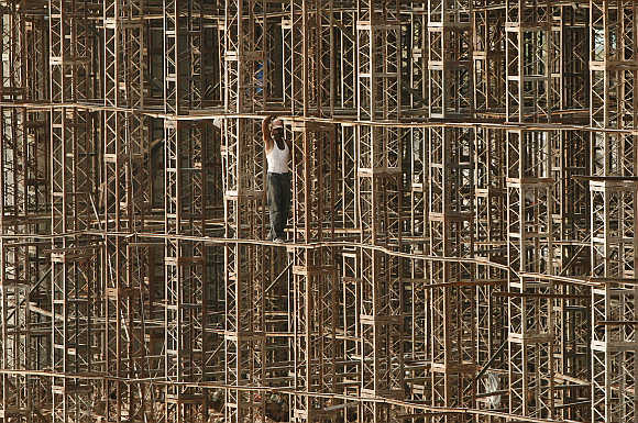 A worker stands on scaffolding at the construction site of a bridge on the outskirts of Jammu.