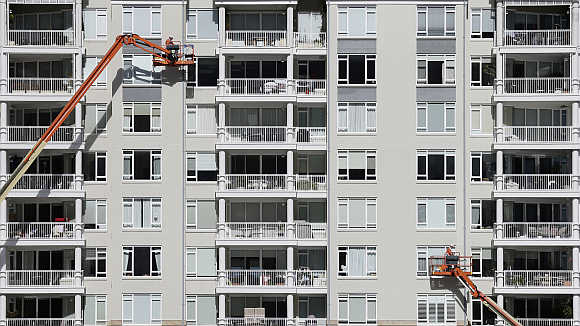 Construction workers put the finishing touches to an apartment building in Sydney.