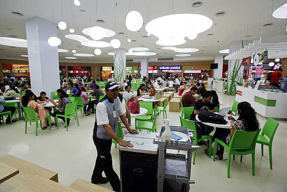 A cleaner pushes a trolley as customers eat at the foodcourt of a shopping mall in Mumbai.