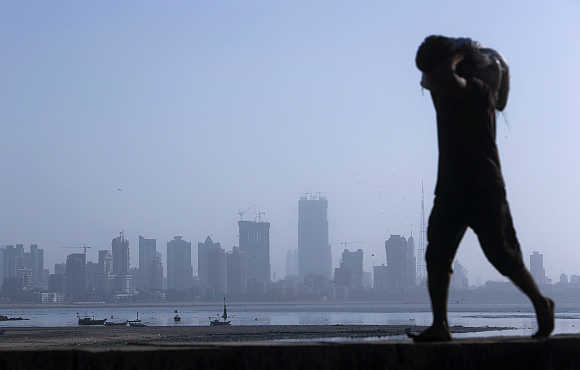 A labourer carries a sack of cement against a backdrop of the central Mumbai financial district.