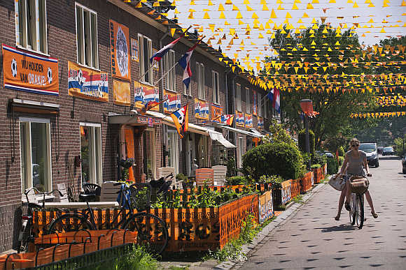 A woman rides her bicycle through the orange-decorated Orion street in Amsterdam.