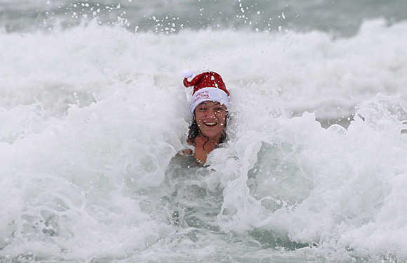 A woman enjoys the waves on a cold and windy Christmas day at Bondi beach in Sydney.