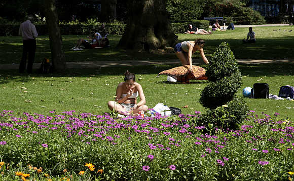A woman reads a book in a garden on a sunny day in downtown London.