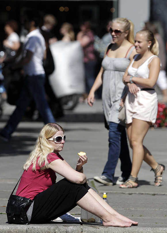 A woman eats in a square in Oslo.
