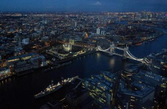 Tower Bridge and the Canary Wharf financial district are seen at dusk in an aerial photograph.