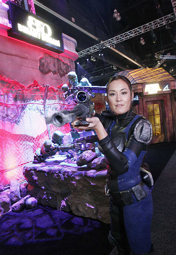 A woman dressed in a combat outfit points a weapon as she promote SciFi game Binary Domain from Sega at E3 in Los Angeles, California.