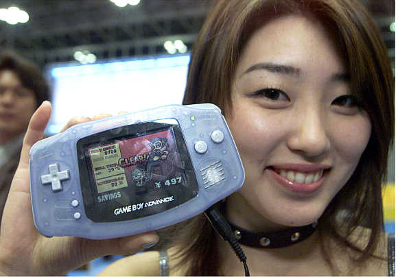 A Nintendo promotion woman shows off the next-generation hand-held console Game Boy Advance in Tokyo, Japan.