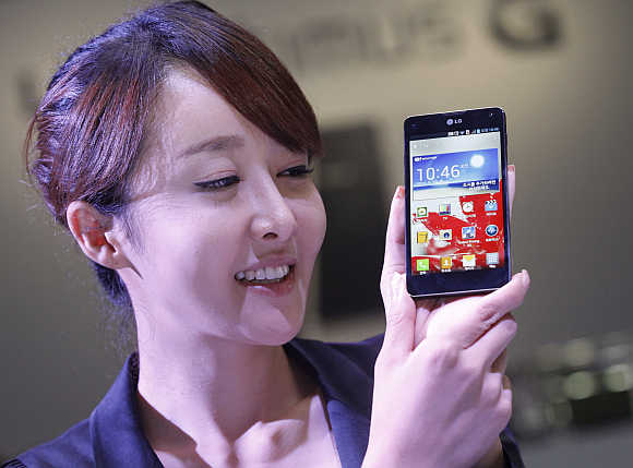An employee of LG Electronics poses with Optimus G smartphone in Seoul, South Korea.
