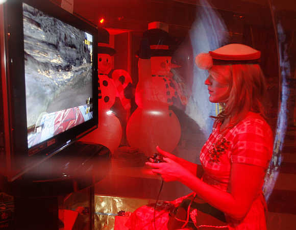A woman in a costume plays a game on the Sony Playstation 3 in Beverly Hills.