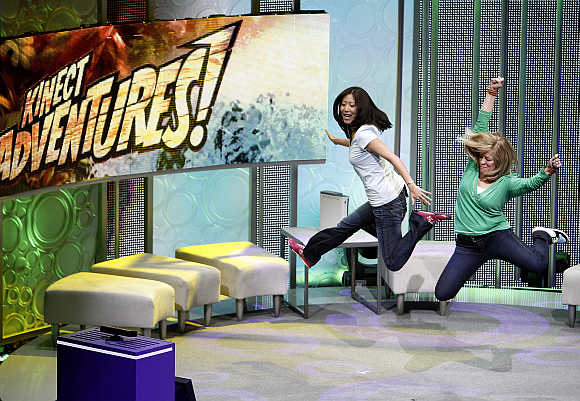 Assistants demonstrate the game Kinect Adventures for Kinect for Xbox 360 in Los Angeles.