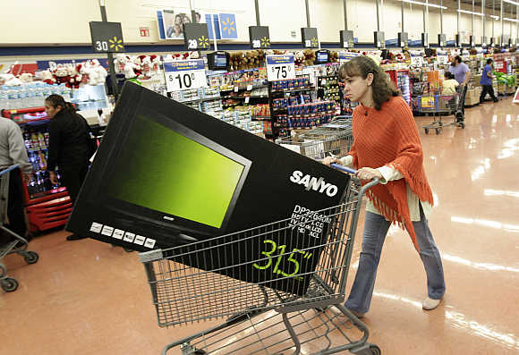 A shopper pushes a cart with a television screen at a Walmart store in Mexico City, Mexico.
