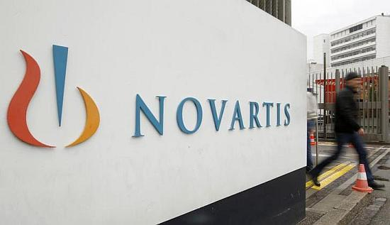 A man walks past the logo of Swiss drugmaker Novartis AG.