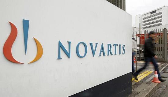 A man walks past the logo of Swiss drugmaker Novartis AG.