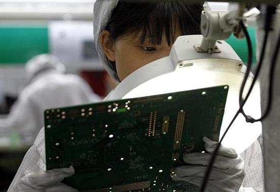 A worker examines a circuit board at an Apple's contract manufacturer. Apple chips are based on ARM's architecture.
