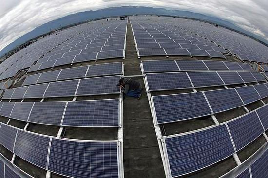 A photographer takes a picture of solar panels.