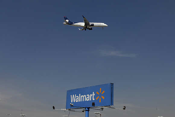 An aeroplane flies over a Walmart billboard in Mexico City, Mexico.