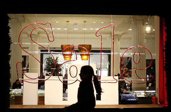 A woman walks past a sale sign in a shop window of Oxford Street in London.