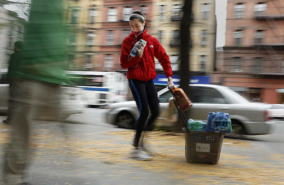 A woman drags a basket full of bottled water down 7th Ave in New York.