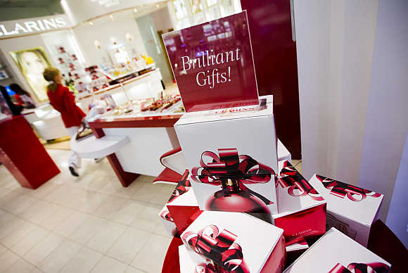 A woman walks behind a Christmas display that reads Brilliant Gifts at a shopping mall in Toronto, Canada.