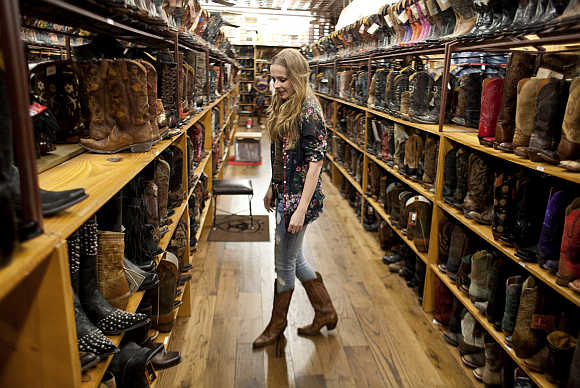 Cristina Grace arranges merchandise in Allen's Boots on South Congress in Austin, Texas.