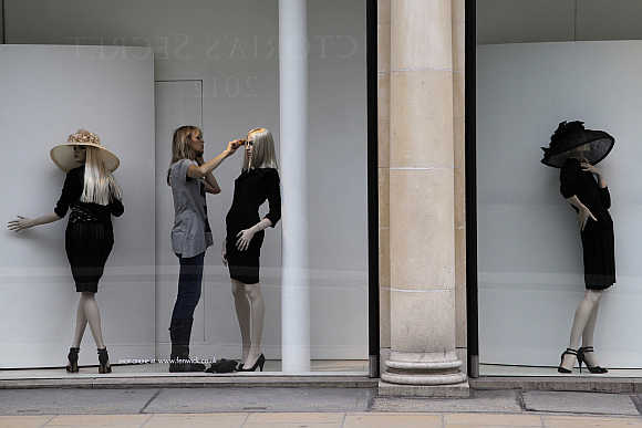 A woman combs the hair of a mannequin in a shop window in Mayfair, London.