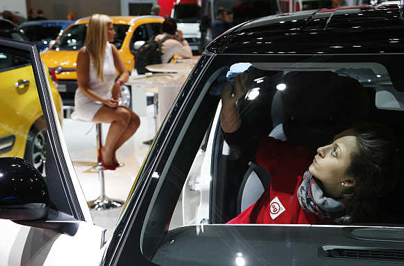 A worker cleans the windshield of a car next to a model during the European Motor Show in Brussels, Belgium.