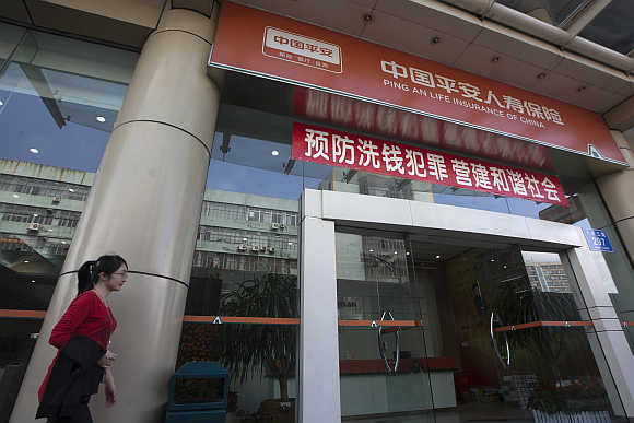 A woman walks past a Ping An Insurance building in Shenzhen.
