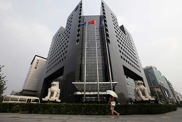 A woman walks in front of the China Construction Bank headquarters building in Beijing.