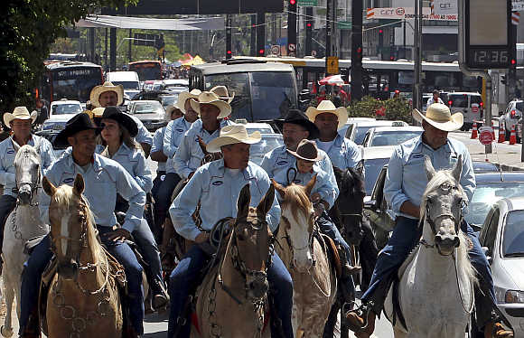 People ride horses along a main avenue in the financial centre of Sao Paulo.