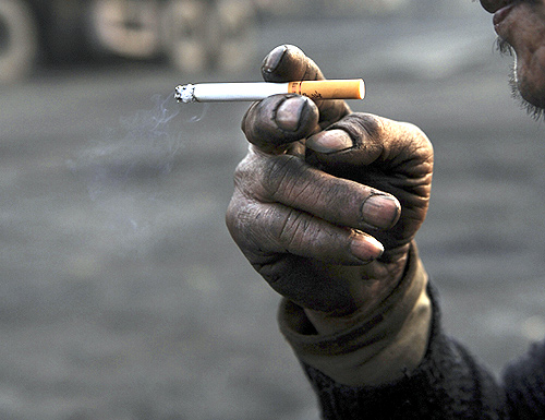 A worker smokes a cigarette during a break at a coal freight yard.