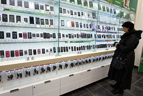A customer looks at a display of handsets for sale.